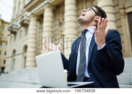 Excited businessman with laptop looking upwards and expressing gladness