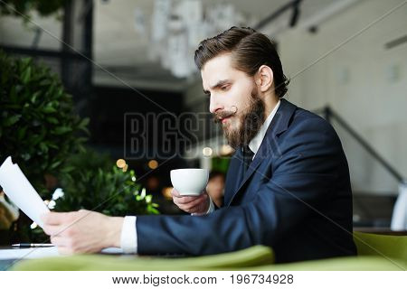 Busy financier having coffee and reading business papers