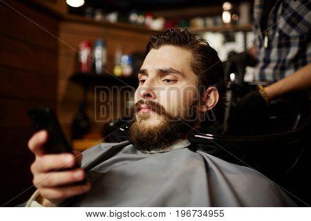 Modern man with smartphone sitting in barbershop