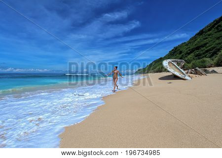 A young woman in bikini runs along an ocean beach with waves.On the beach lie the wreckage of a boat