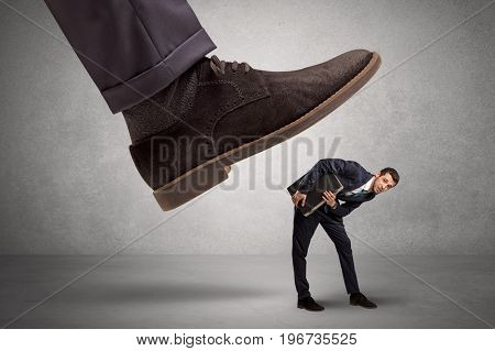 Employee is afraid of the big boss foot, which is stepping down him