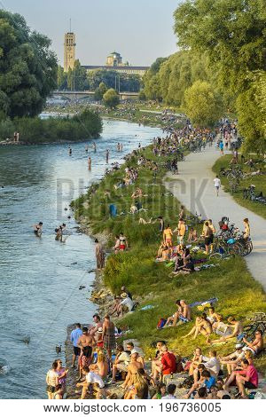 Unidentified people enjoy the sunset on Isar river on July 07 2015 in Munich Bavaria Germany.