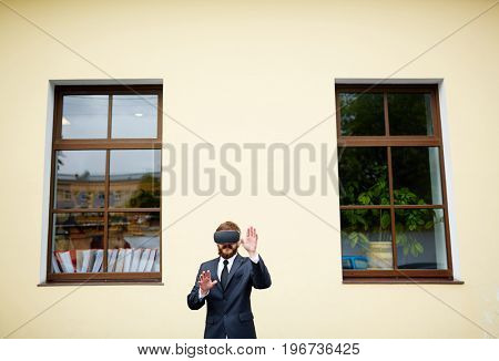 Businessman with vr headset against house