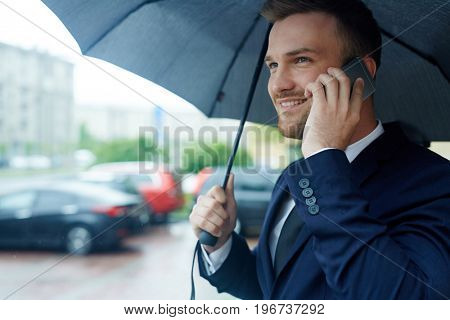 Successful leader making appointment on the phone on rainy day