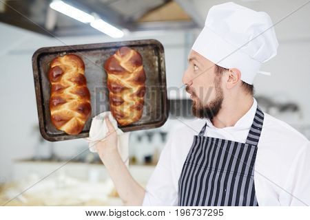 Amazed baker holding hot tray with just baked buns