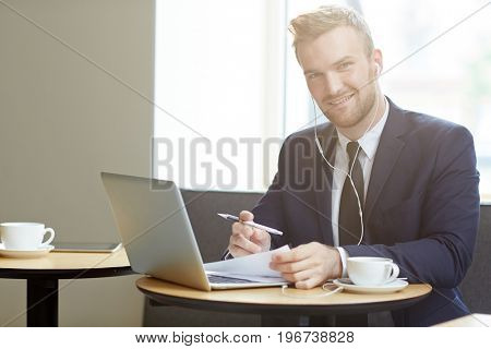 Young successful broker with earphones working by table in front of laptop