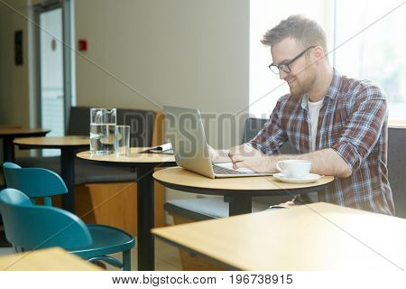 Young designer working online while sitting in cafe