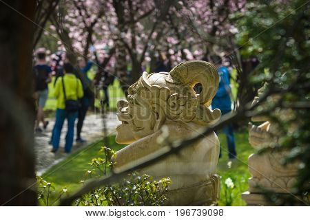 Korean tradition stone idol in the flowered spring park. A view through the trees.