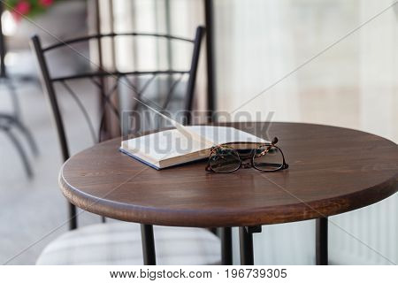 Book on the table in summer cafe