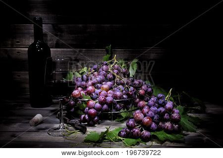 Fresh red grapes bunch lying on leaves on an old wooden table. Photographed with light painting technique