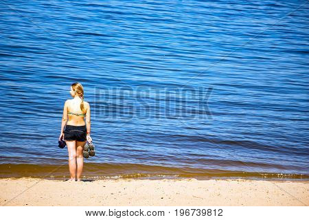 A girl is standing on the sea shore or river