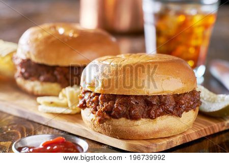 two sloppy joes with potato chips and pickles on wooden serving tray