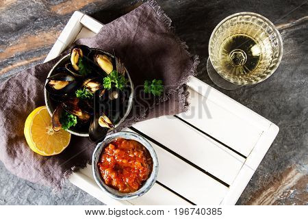 Mussels With Herbs In A Bowl With Lemon And Wine On A White Wood