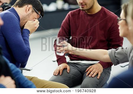 Woman giving glass of water to crying man