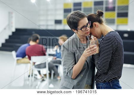 Crying girl keeping her head on shoulder of psychologist