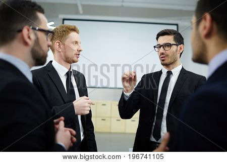Group of businessmen listening to colleague after conference