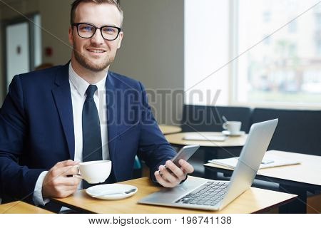 Smart manager having coffee break in cafe