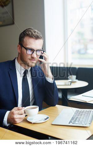 Businessman talking on smartphone by cup of tea