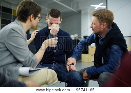 Friends supporting crying man during psychological session