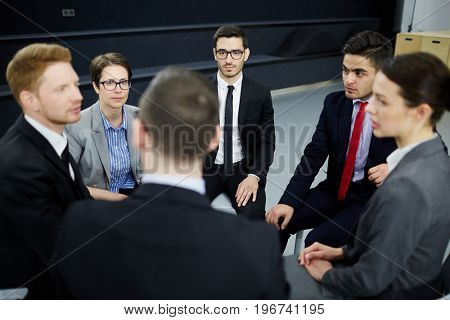 Business people sitting in circle and having discussion