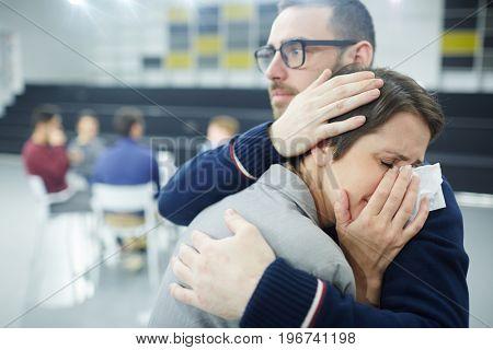 Desperate female crying on man shoulder