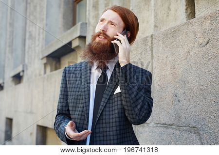 Smart businessman in suit phoning outdoors
