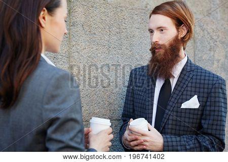 Elegant man with beard talking to colleague at coffee-break