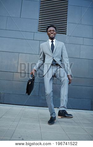Ecstatic businessman dancing in urban environment against wall of building