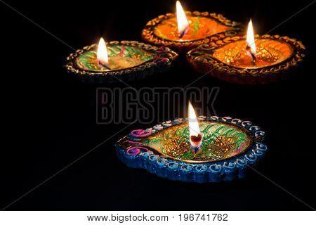 Four burning colorful candles indian style for Diwali celebration on black background.