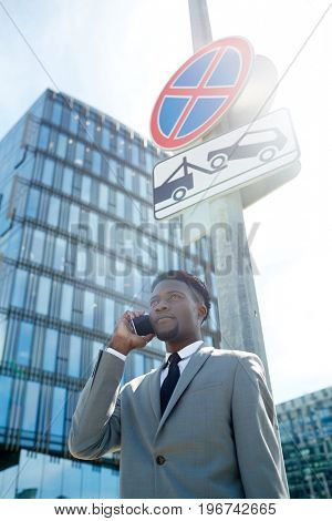 Businessman calling under warning sign outdoors