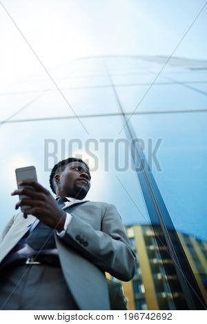Man with smartphone waiting for business partner outdoors