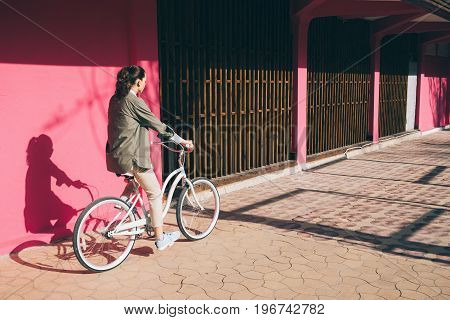 Woman in a jacket rides a city bike against the background of a pink wall