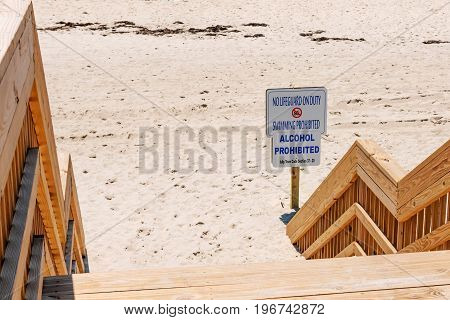Steps leading down to the beach on Fire Island with a sign that reads No Lifeguards On Duty Swimming Prohibited Alcohol Prohibited