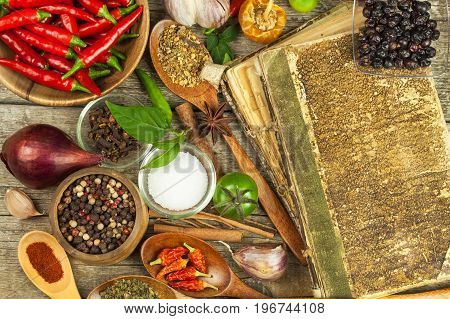 Old book of cookery recipes. Culinary background and recipe book with various spices on wooden table