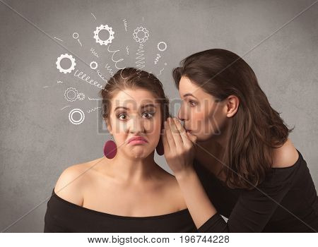 Two girlfriends in elegant black dress sharing secrets with each other concept with drawn rack cog wheels and spiral lines on the wall background.