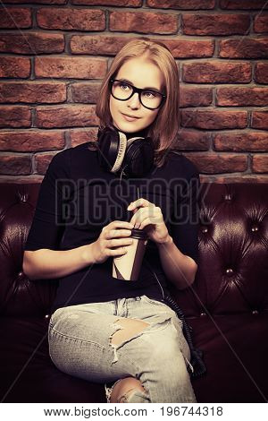 Cute young woman having a rest with a cup of coffee. Loft style interior.