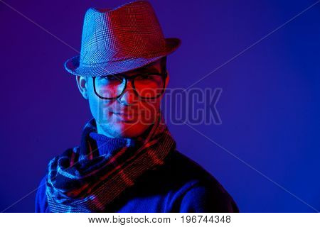 Portrait of a handsome elegant man in blue and red light. Male beauty, fashion.
