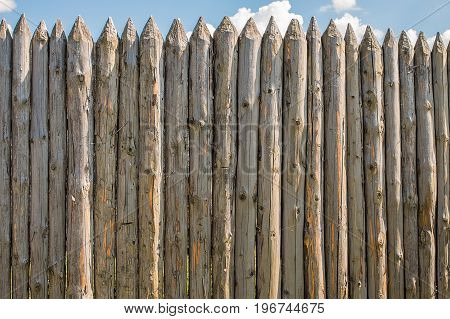 A fence made of old cracked logs against the blue sky