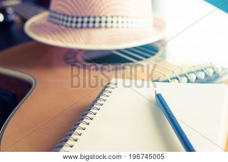 Blank notebook on acoustic guitar for songwriter