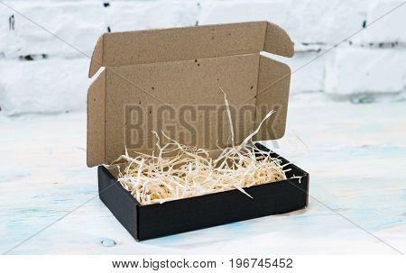 Black gift cardboard box with wooden shavings