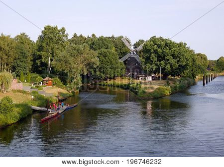 Meppen windmill sits in distance with people from rowing club on left hand side of photo.