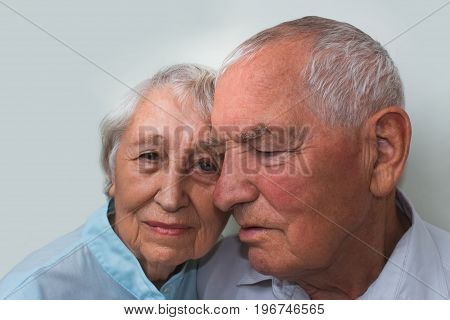 The happy elderly couple on the studio background with eyes closed. Concept of dreams