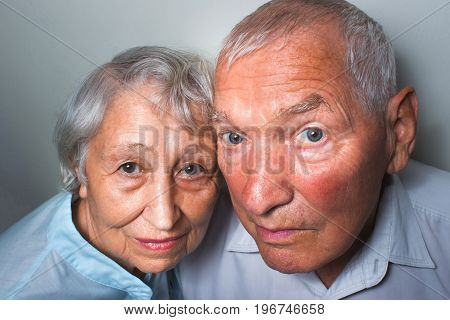 The surprised elderly couple on the studio background