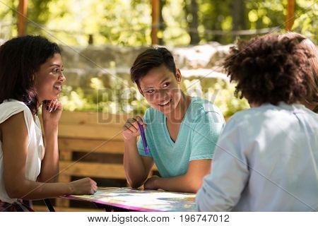 Image of concentrated young multiethnic friends students outdoors studying and talking with each other. Looking aside.