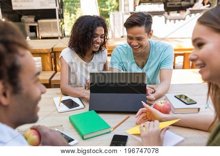 Picture of cheerful young multiethnic friends students outdoors using tablet computer and talking with each other. Looking aside.