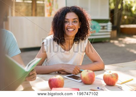 Picture of smiling young african lady sitting at the table near friends outdoors. Looking at camera.