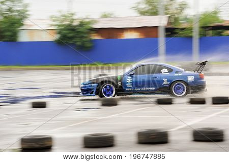 Orel Russia July 22 2017: Dynamica car festival. Tuned car riding swiftly along tyre line with water splashes motion blur