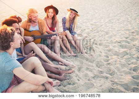 Happy group of friend having party and playing guitar on the beach