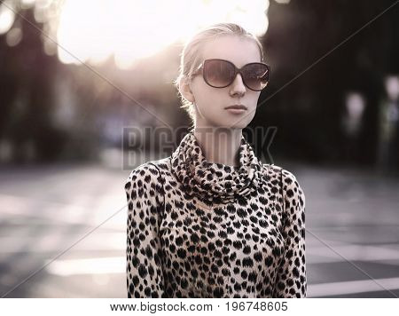 Fashion lady woman wearing a leopard dress with sunglasses at evening city