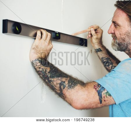 Repairman working with measuring ruler on the wall